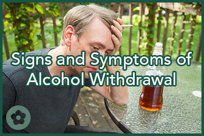 Sad man sitting at table with alcohol and holding cigarette