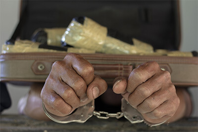 Drug traffickers were arrested along with their heroin. Police arrest drug trafficker with handcuffs.